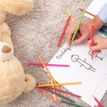 Close up of hands of father and his child are drawing picture of themselves. They are holding colored pencils. The man and boy are sitting on flooring